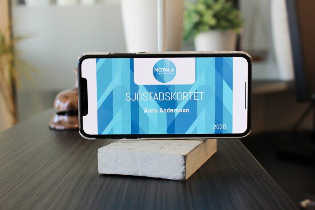 Smartphone står på bord med ett sjöstadskort på skärmen.